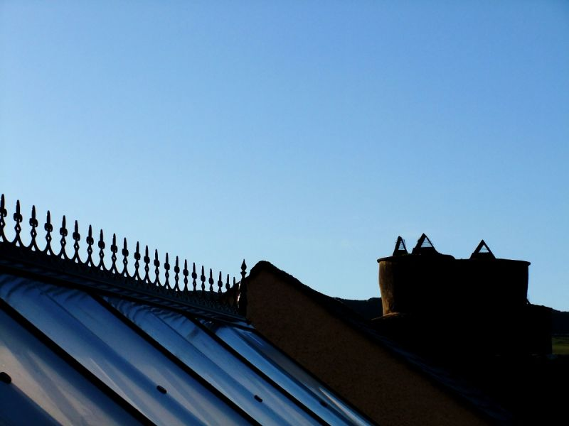 roof and chimney silhuoetted against blue sky