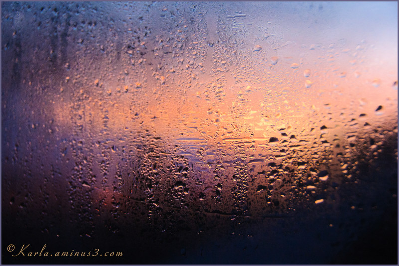 Sunset seen through water on window