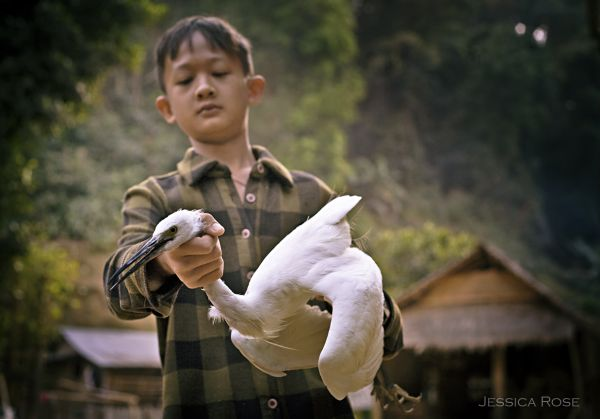 A young boy shows off the heron he caught