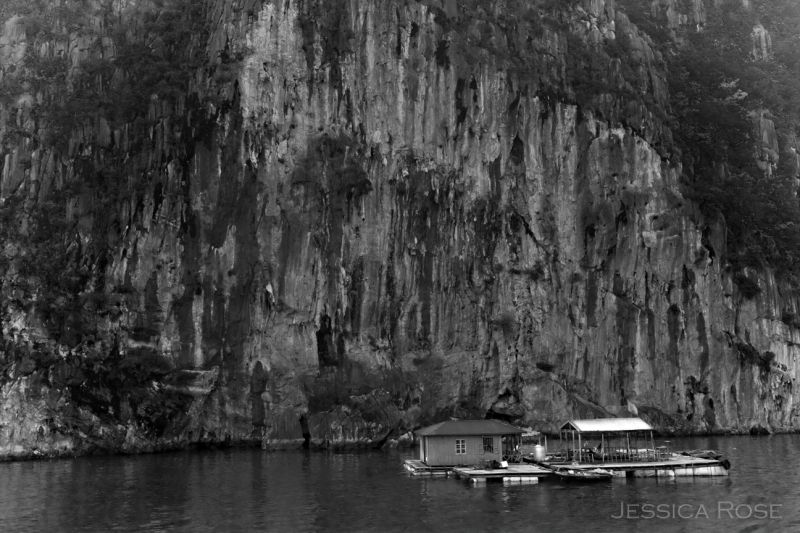 The house of a fisherman is dwarfed by cliffs