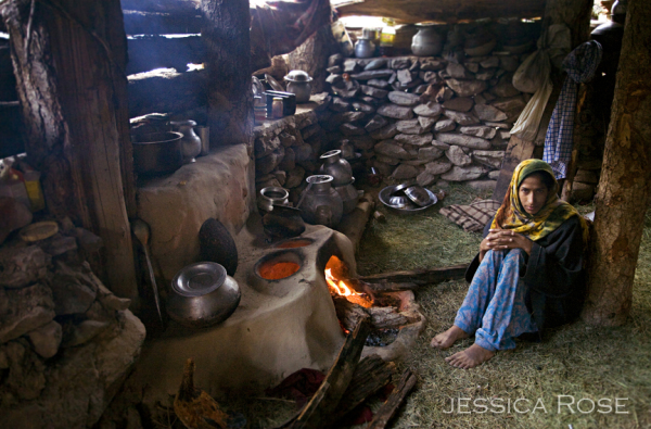 A Gujar woman poses next to the hearth in her home