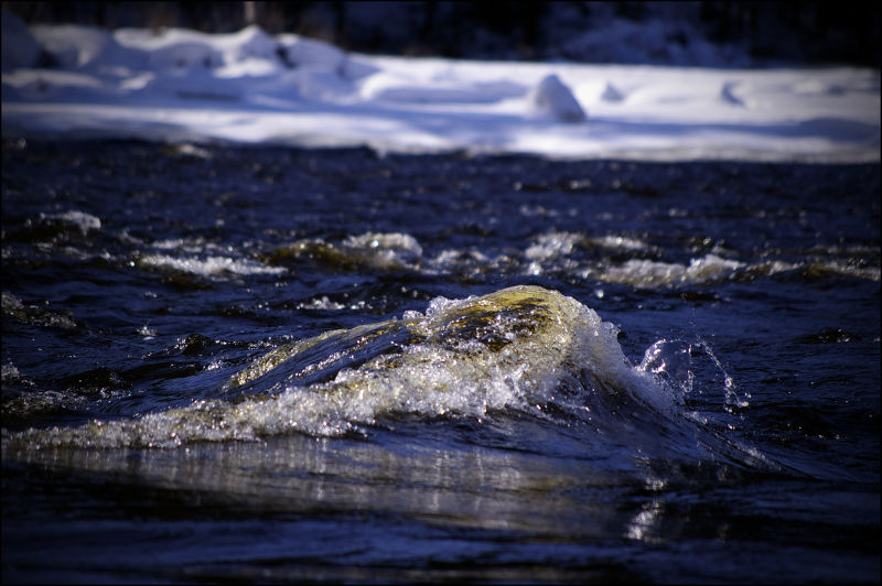 A large wave of water with ice in background