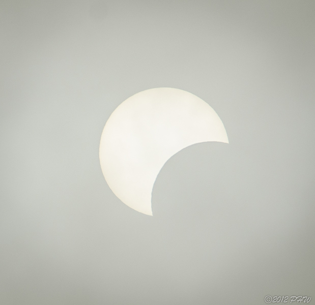 Sunday May 20th. 6PM Pacific Time. I stepped out the back door & in the heavy overcast above me there was an eclipse underway. I had no idea this eclipse was to happen. As luck had it I had my camera with me. I used my 18-250mm. lens fully zoomed in. I've cropped it but other than that this is how it appeared.