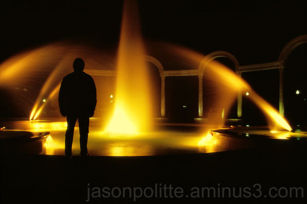 Mysterious man silhouetted against a fountain