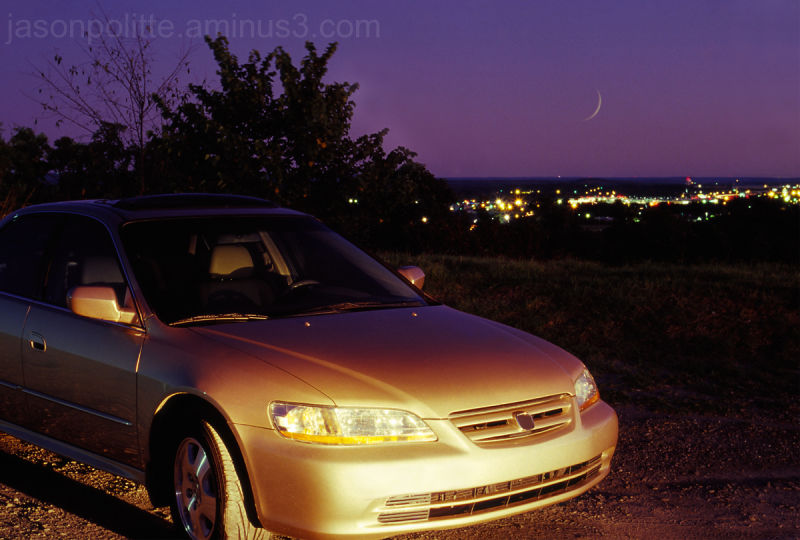 Honda car with moon and city skyline at twilight