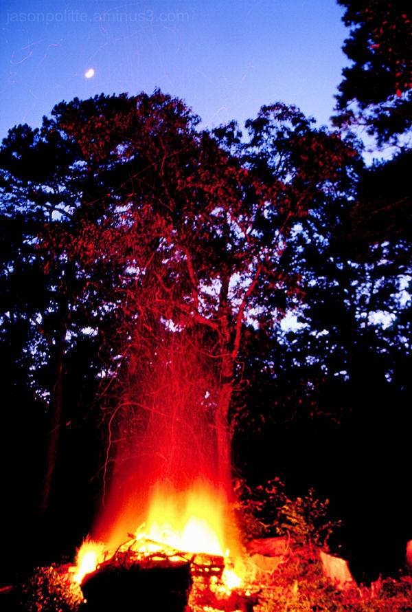 A half moon rises above this large bonfire