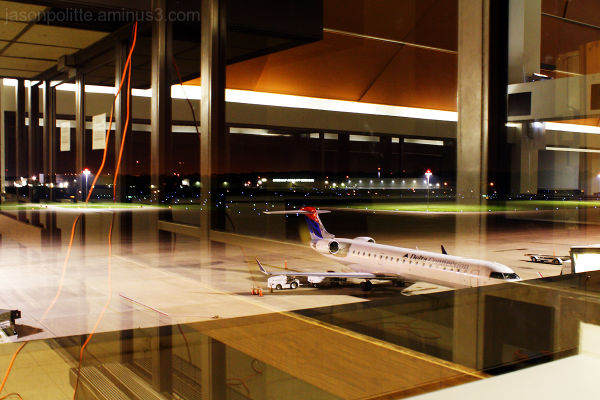 Delta Airliner at terminal seen through reflection