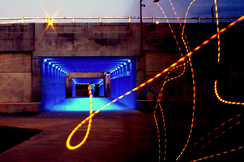 Playing with light as a bystander walks in tunnel