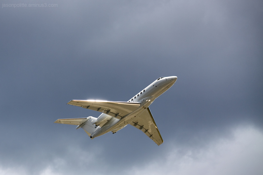 Sunlit private jet passing under dark clouds