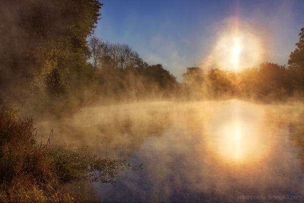 Steam eminates from the water as the sun rises