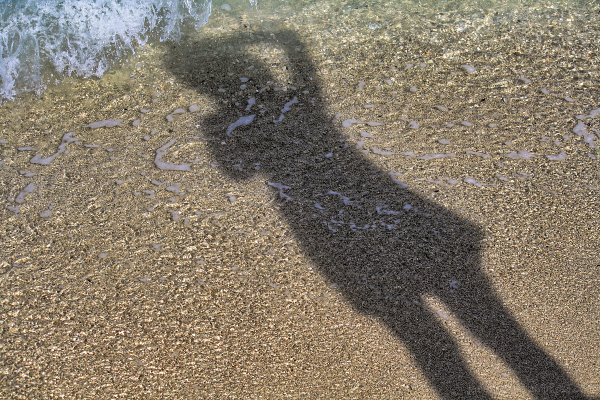 Shadow of a woman holding onto her hat.
