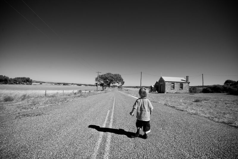 A boy wandering a lonely country road