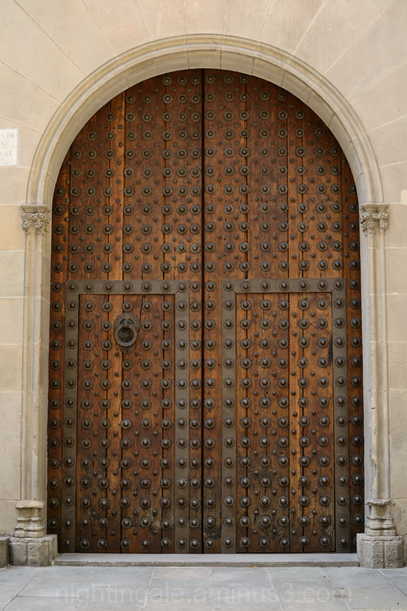 An arched, studded, wooden door in Barcelona ...