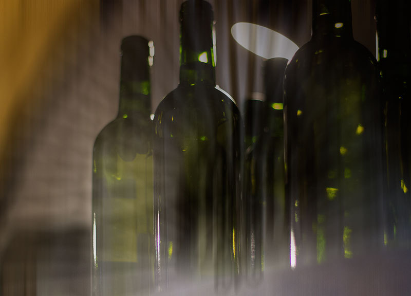 green bottles in dark cellar