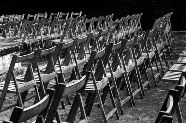 rows of wooden chairs in black and white outdoor