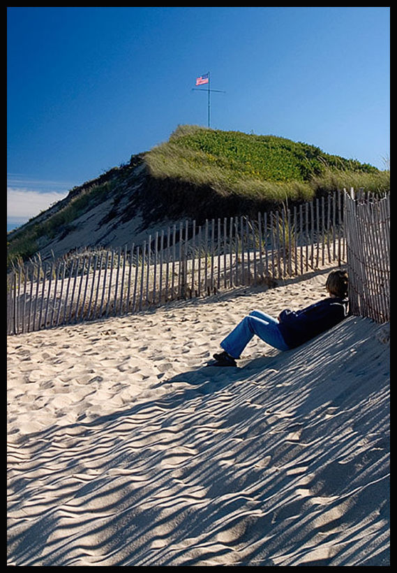 A beach goer enjoys a quiet moment in Cape Cod
