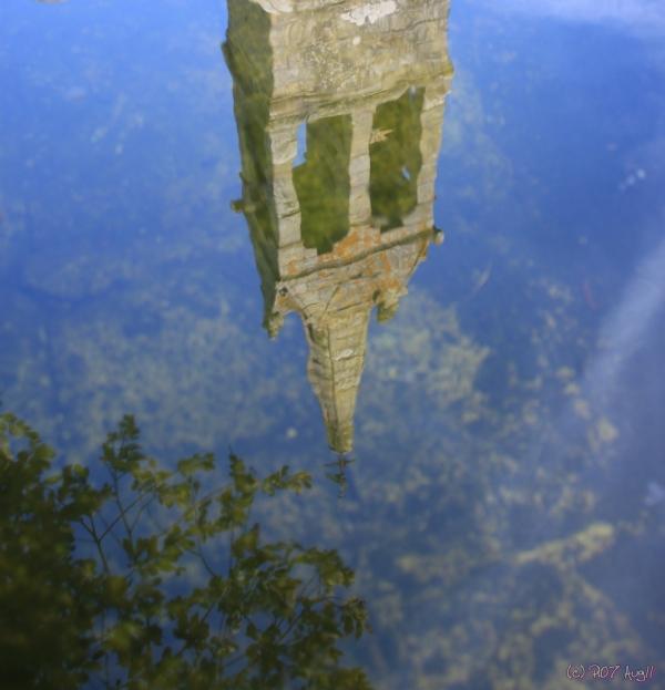 reflet d'un clocher dans un lavoir