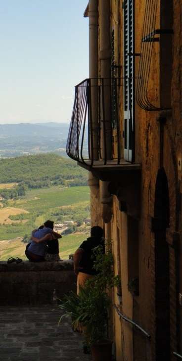 Lovers embrace overlooking the tuscan vneyards