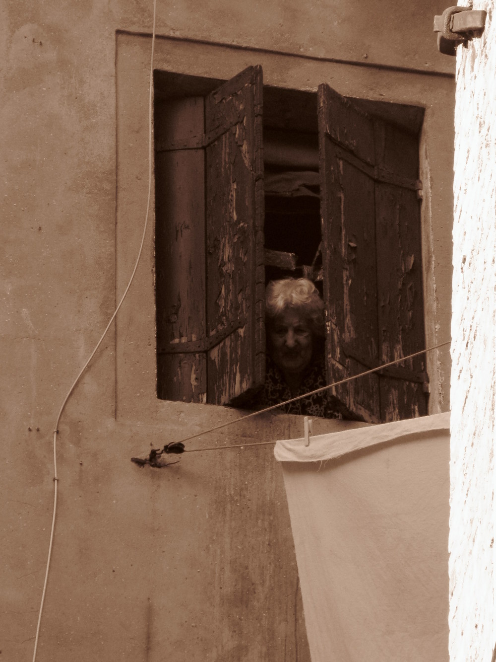 Old woman at a window in Venice
