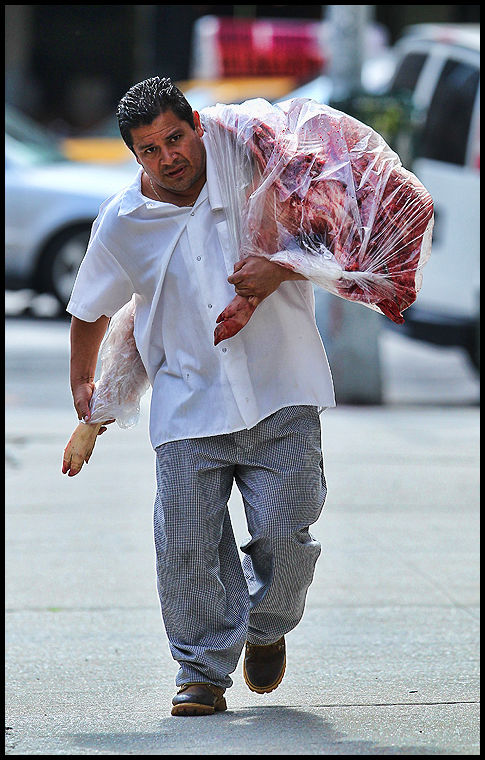 Butcher carries a slaughtered pig to East Village