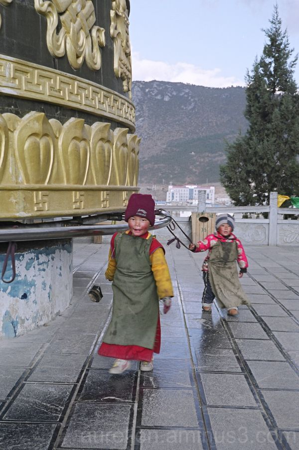Two Tibetan Children Turning a Giant Prayer Wheel