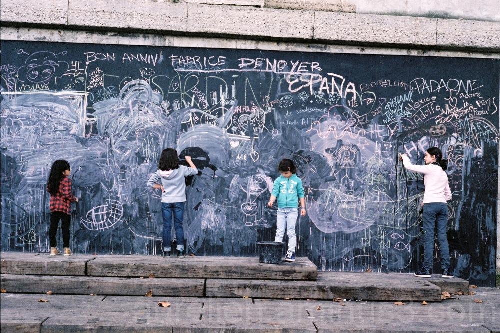 Four kids writing on an outdoor blackboard