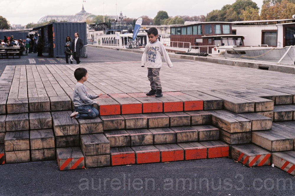 Two kids playing on red crates