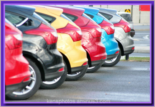 colourful row of cars for sale.