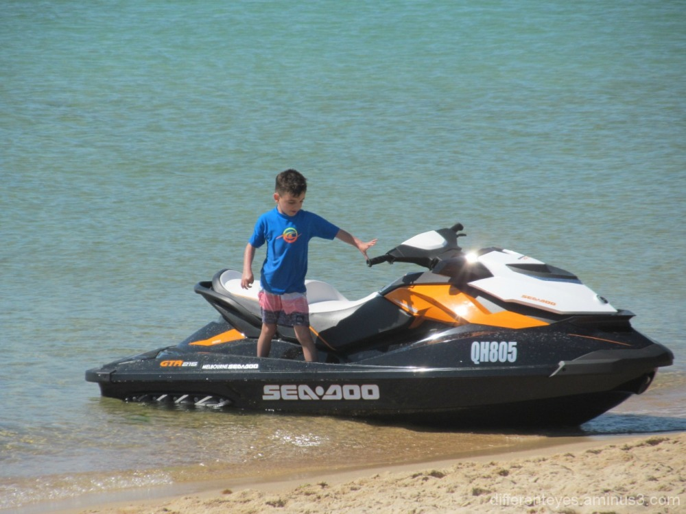 child checking a jetski at Dromana beach