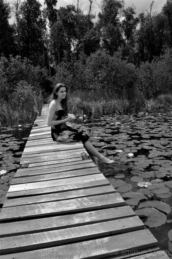 girl sitting on dock with lily flower