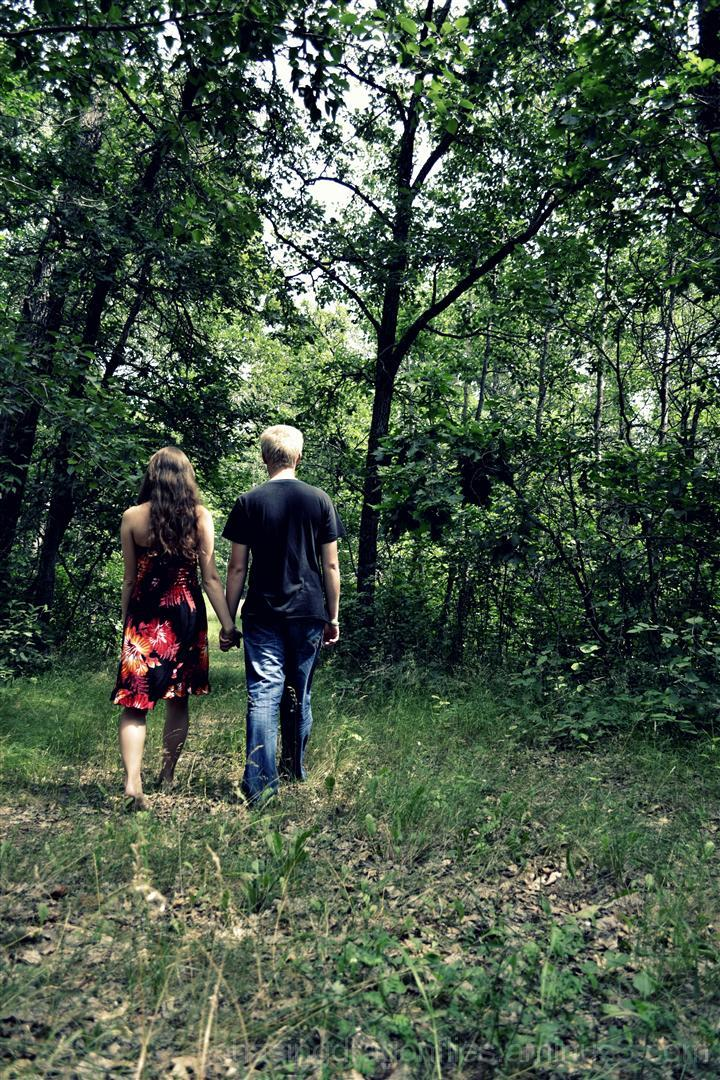 couple holding hands walking through woods