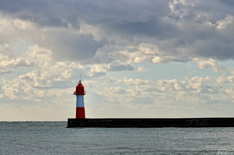 The sea, a lighthouse, clouds