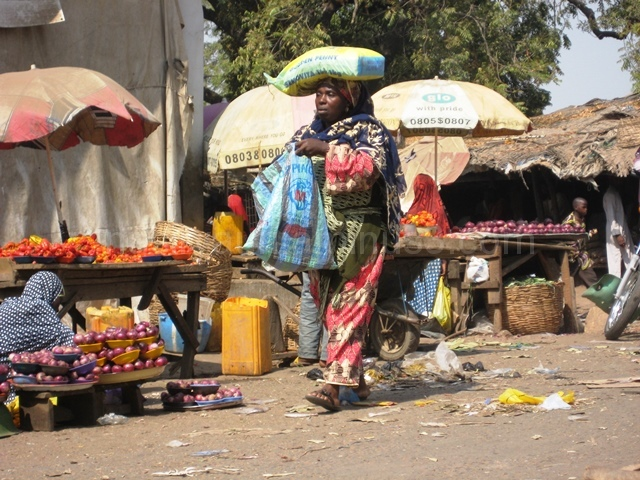A WOMAN CARRYING LOAD