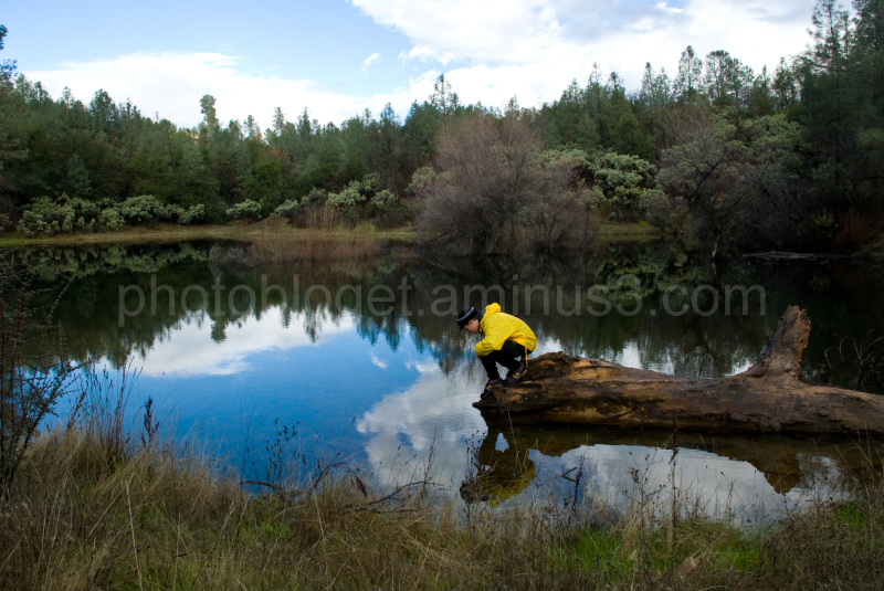 man looking in water at reflection