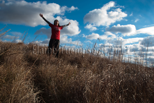 woman holding arms spread wide on top of a hill