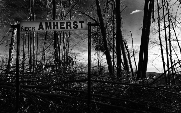 Sign to the Amherst stop along train tracks