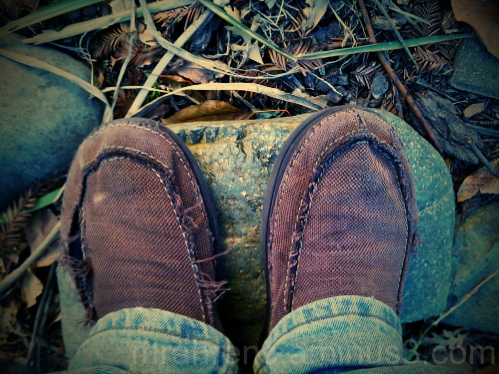 Torn shoes standing on a rock