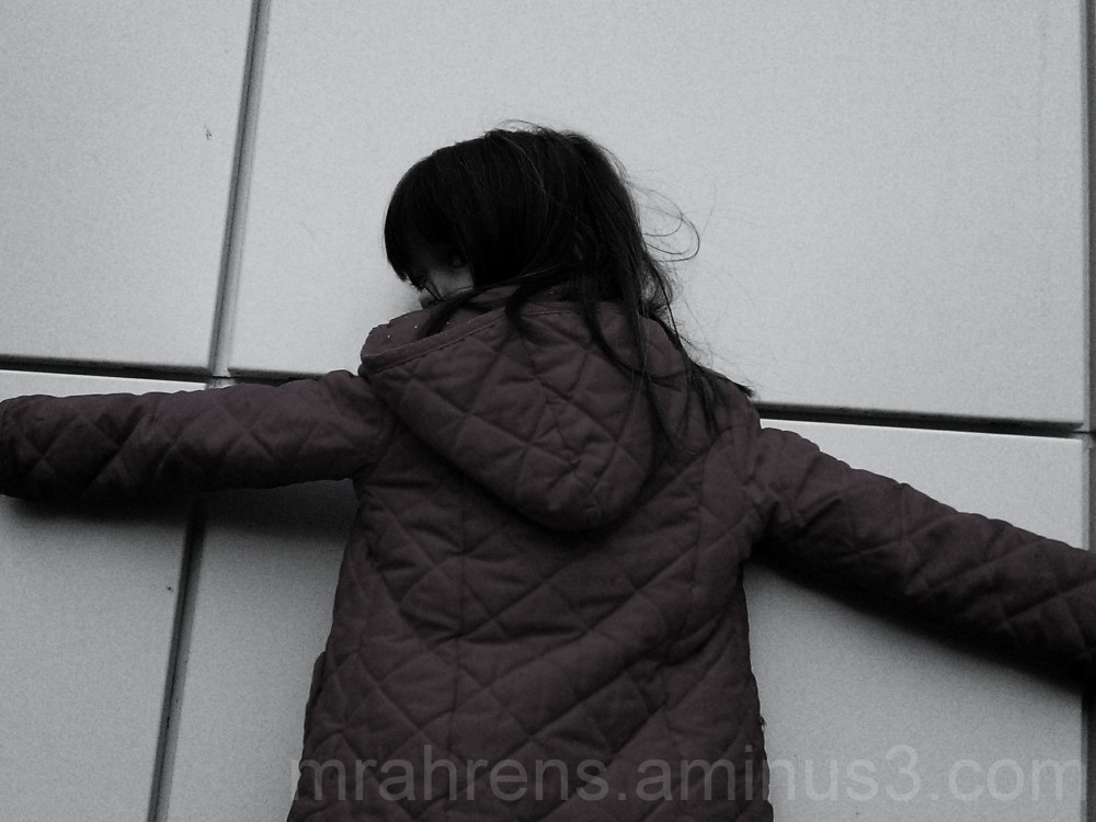 A young girl holds closely to the wall.