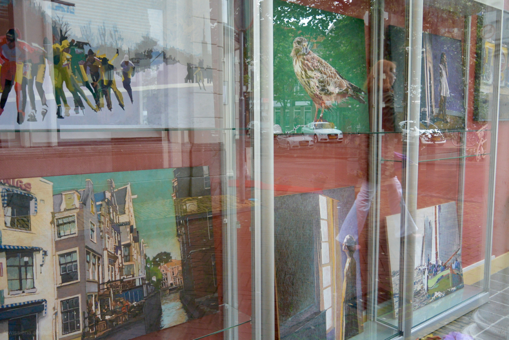 paintings on display window reflection