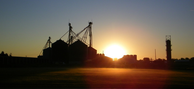 Sunrise behind Grain Bins