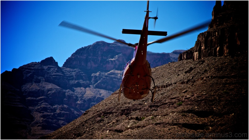 Helicopter flying out of canyon