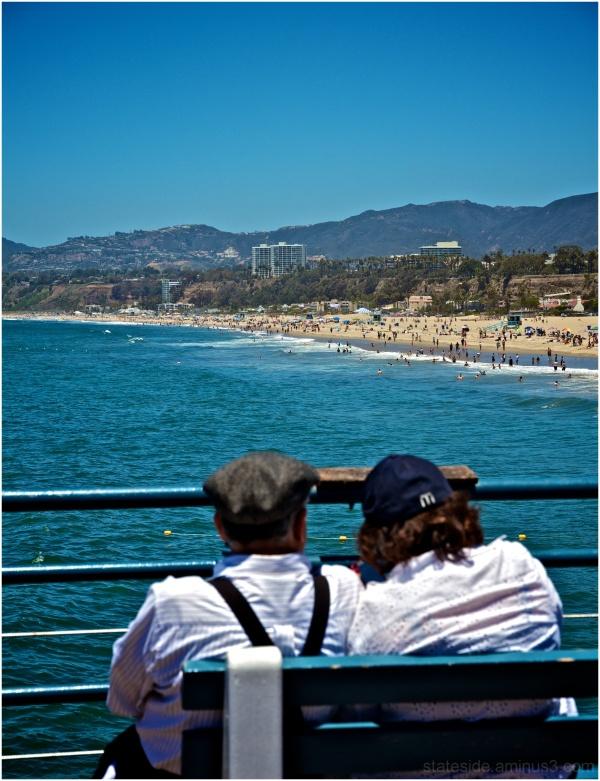 Couple sit and watch Santa Monic beach goers