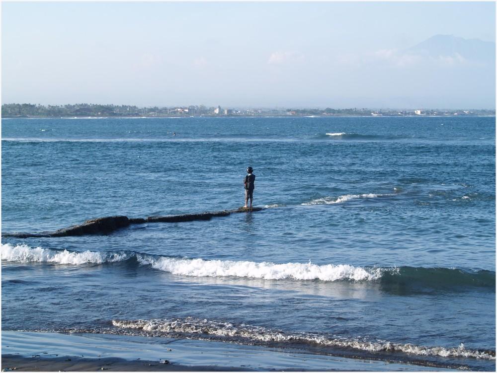 Pêcheur casqué en bord de mer