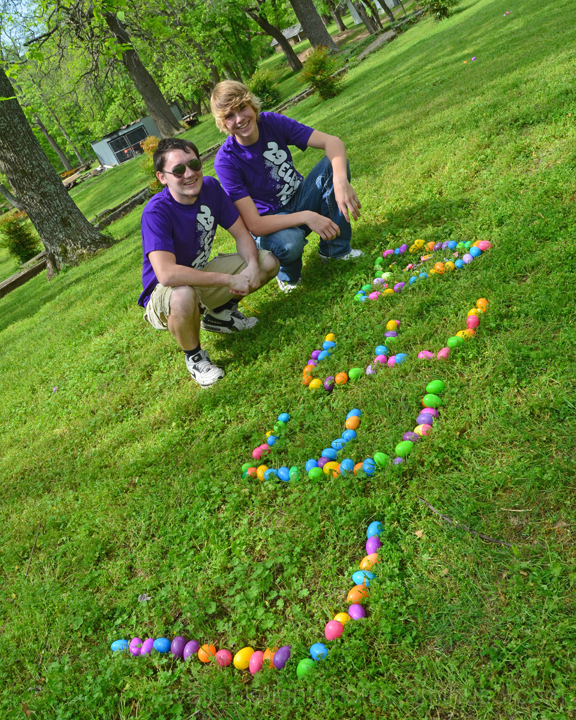 Two boys spell out name with Easter eggs