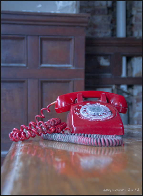An old fashioned red rotary phone on a wooden desk
