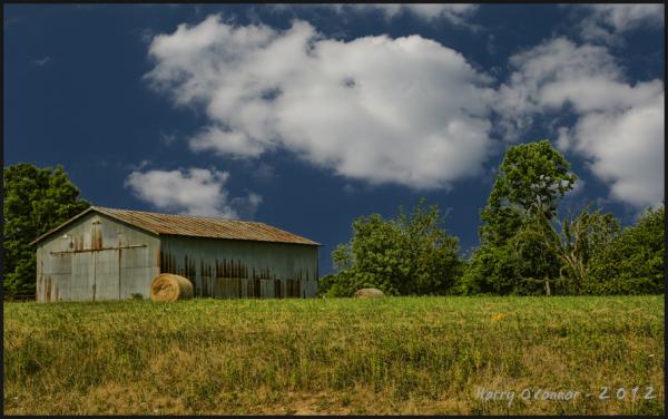 Round bales of hay near a rusty barn