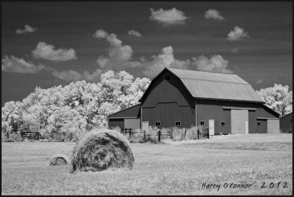 Rural scene with round bales and a barn