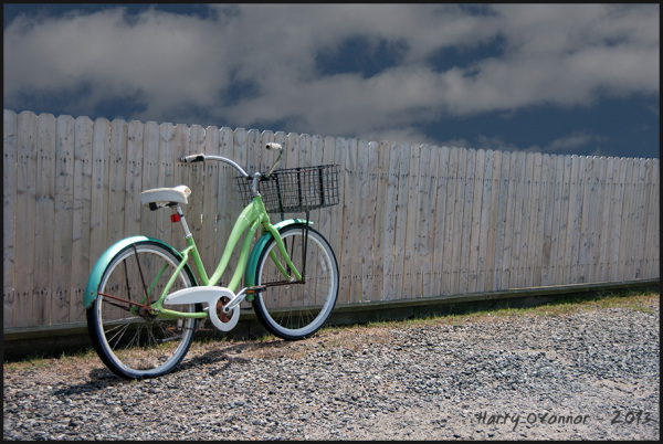 Green bike and fence