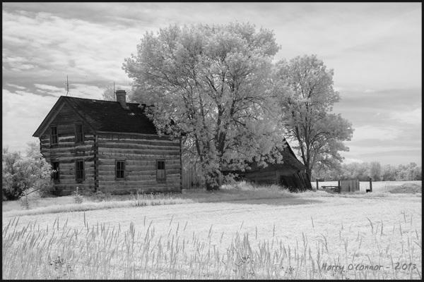 Log farmhouse with barn