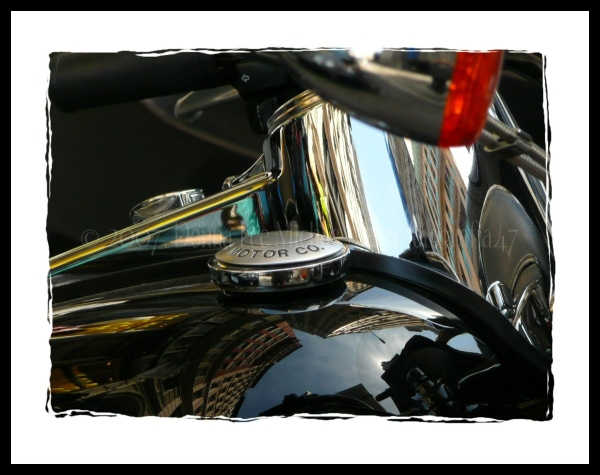 Warped reflection of NYC buildings on motorcycle.